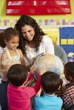 Gruppo di scolari elementari di età nella classe con l'insegnante Fotografia Stock Libera da Diritti
