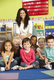 Gruppo di scolari elementari di età nella classe con l'insegnante Immagine Stock