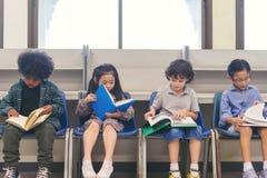 Gruppo di scuola materna, di ragazzi del piccolo bambino e di ragazza leggenti un libro all'aula fotografia stock