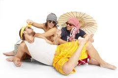 Gruppo di seduta dei giovani. Tema della spiaggia Fotografie Stock