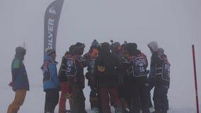 Gruppo di soggiorno degli snowboarders sul pendio nevoso Sfida di concorso Stazione sciistica nebbia archivi video