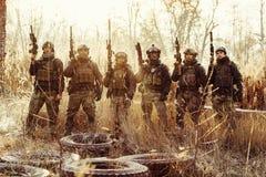 Gruppo di soldati che stanno con le armi e che esaminano la macchina fotografica immagini stock libere da diritti