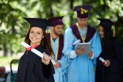 Gruppo di studenti in abiti di graduazione Immagine Stock