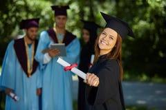 Gruppo di studenti in abiti di graduazione Fotografie Stock