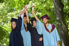 Gruppo di studenti in abiti e cappucci di graduazione Immagini Stock Libere da Diritti