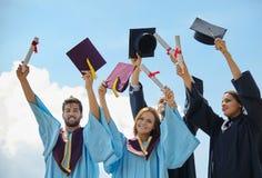 Gruppo di studenti in abiti e cappucci di graduazione Immagine Stock Libera da Diritti
