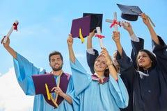Gruppo di studenti in abiti e cappucci di graduazione Fotografia Stock Libera da Diritti