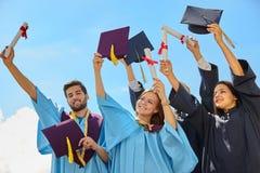 Gruppo di studenti in abiti e cappucci di graduazione Fotografie Stock