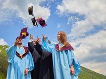 Gruppo di studenti in abiti e cappucci di graduazione Immagine Stock