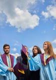 Gruppo di studenti in abiti e cappucci di graduazione Fotografia Stock