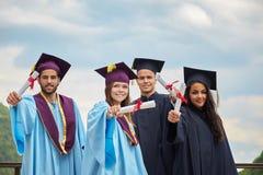 Gruppo di studenti in abiti e cappucci di graduazione Immagini Stock
