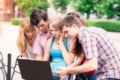 Gruppo di studenti adolescenti sorridenti felici fuori dell'istituto universitario Immagine Stock