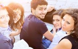 Gruppo di studenti allegri con un computer portatile un fondo dell'istituto universitario un giorno soleggiato Immagine Stock Libera da Diritti