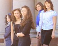 Gruppo di studenti allegri sui precedenti del giorno soleggiato dell'istituto universitario Immagine Stock Libera da Diritti