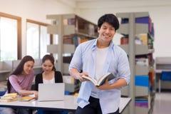 Gruppo di studenti asiatici che studiano insieme nella biblioteca, imparare immagine stock