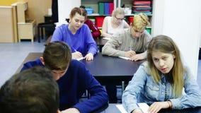 Gruppo di studenti che ascoltano l'insegnante che spiega materiale nella classe stock footage