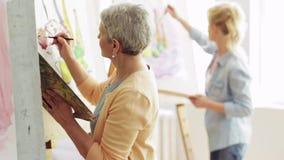 Gruppo di studenti che dipingono allo studio della scuola di arte stock footage
