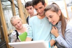 Gruppo di studenti che esaminano computer portatile Fotografie Stock Libere da Diritti