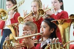Gruppo di studenti che giocano insieme nell'orchestra della scuola fotografie stock libere da diritti