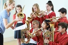 Gruppo di studenti che giocano insieme nell'orchestra della scuola immagine stock