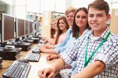 Gruppo di studenti che lavorano ai computer in biblioteca immagine stock