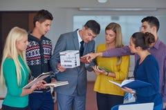 Gruppo di studenti che lavorano con l'insegnante sul modello della casa Fotografie Stock Libere da Diritti