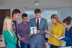 Gruppo di studenti che lavorano con l'insegnante sul modello della casa Immagine Stock Libera da Diritti
