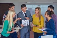 Gruppo di studenti che lavorano con l'insegnante sul modello della casa Immagine Stock