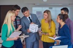 Gruppo di studenti che lavorano con l'insegnante sul modello della casa Fotografie Stock