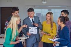 Gruppo di studenti che lavorano con l'insegnante sul modello della casa Immagini Stock