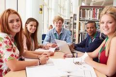 Gruppo di studenti che lavorano insieme nella biblioteca Immagini Stock Libere da Diritti
