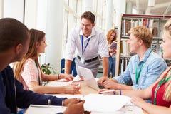 Gruppo di studenti che lavorano insieme nella biblioteca con l'insegnante Fotografie Stock