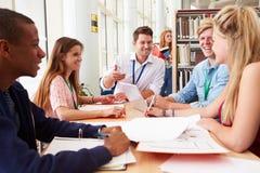 Gruppo di studenti che lavorano insieme nella biblioteca con l'insegnante Immagini Stock