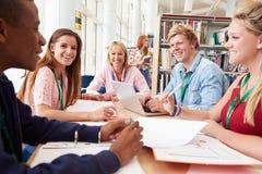 Gruppo di studenti che lavorano insieme nella biblioteca con l'insegnante immagini stock libere da diritti