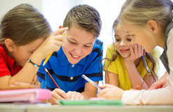 Gruppo di studenti che parlano e che scrivono alla scuola Fotografia Stock