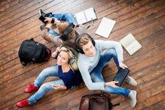 Gruppo di studenti che per mezzo degli smartphones e delle compresse Fotografia Stock