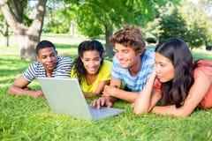 Gruppo di studenti che per mezzo del computer portatile Fotografie Stock Libere da Diritti
