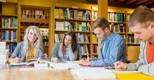 Gruppo di studenti che scrivono le note allo scrittorio delle biblioteche Fotografia Stock