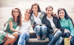 Gruppo di studenti che si siedono con i libri Fotografie Stock