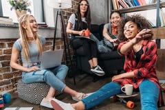 Gruppo di studenti che si siedono insieme al computer portatile ed alla conversazione Fotografia Stock