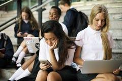 Gruppo di studenti che si siedono sulla scala facendo uso del computer portatile Fotografie Stock Libere da Diritti