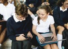 Gruppo di studenti che si siedono sulla scala facendo uso del computer portatile Immagine Stock Libera da Diritti