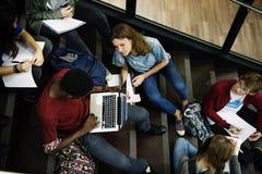 Gruppo di studenti che si siedono sulla scala facendo uso del computer portatile Immagini Stock