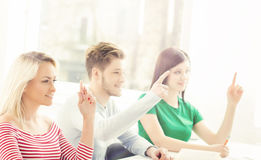 Gruppo di studenti che sollevano le mani in un'aula Fotografia Stock
