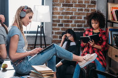 Gruppo di studenti che studiano insieme ai libri ed alla compressa digitale Fotografia Stock