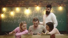 Gruppo di studenti che studiano insieme in un'aula, un gruppo di studente di quattro giovani con l'insegnante nell'aula della scu archivi video