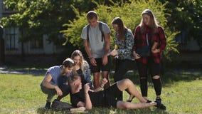 Gruppo di studenti che svegliano amico sonnolento in parco archivi video