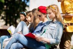 Gruppo di studenti con i taccuini al cortile della scuola Immagini Stock