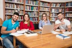 Gruppo di studenti con il computer portatile in biblioteca Immagine Stock