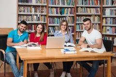 Gruppo di studenti con il computer portatile in biblioteca Fotografie Stock
